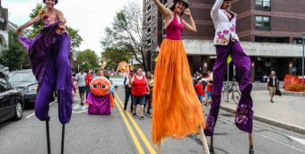 three people walk on stilts, wearing bright, flowing pants, down a closed city street as part of IBA's Festival Betances