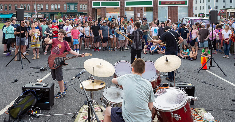 A band of four musicians play on asphalt in a parking lot as a standing crowd encircles them