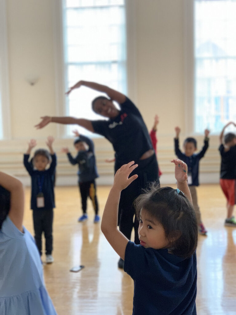 Young girl in a dance class looks over her left shoulder.