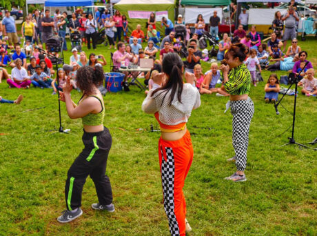 3 woman prepare to perform in front of a crowd seated in the grass in front of a row of tents