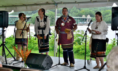 Four performers in native dress on a stage sing and play instruments