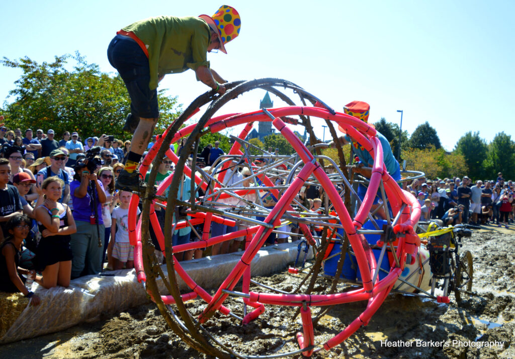 two people working to get their kinetic sculpture through a patch of mud during the Lowell Kinetic Sculpture Race