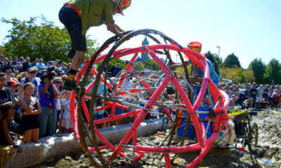 two people working to get their kinetic sculpture through a patch of mud while during the Lowell Kinetic Sculpture Race.