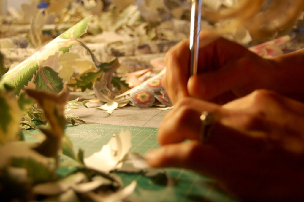 close up of an artist holding an exacto knife, cutting paper in the foreground, a pile of cut-out paper in the background