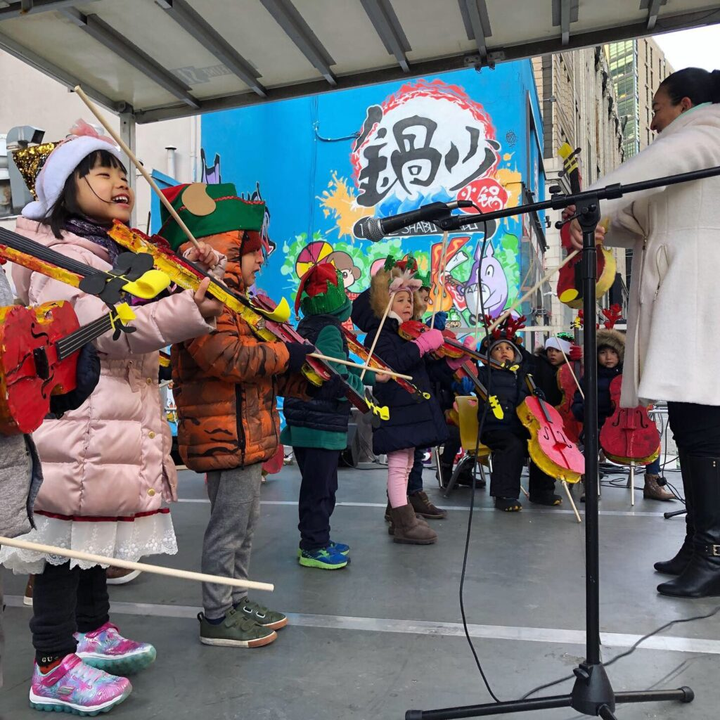 Children wearing winter hats and coats playing stringed instructments while performing outside