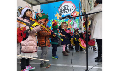 Children wearing winter hats and coats playing stringed instruments while performing outside.