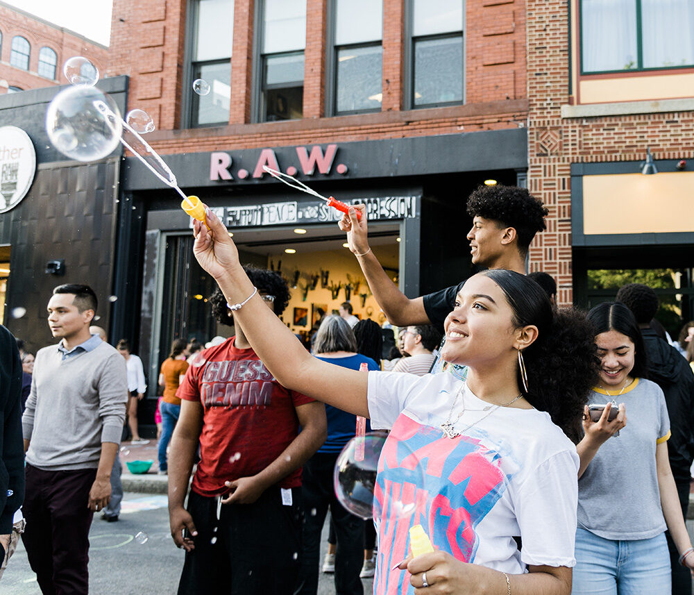 a group of young people blowing bubbles in front of Raw Art Works