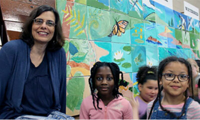 A woman and two children stand in front of a mural they made at May Street School