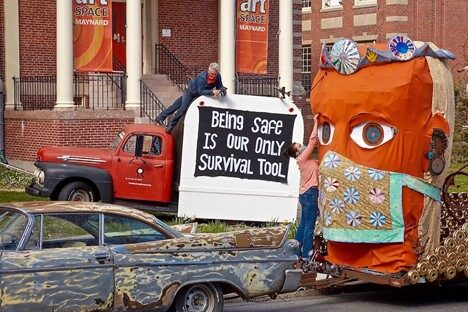 """a pickup truck with a sign reading """"being safe is our only surival tool"""" next to a 10ft tall sculpture on a trailer of a head wearing a bejeweled crown and floral cloth mask"""