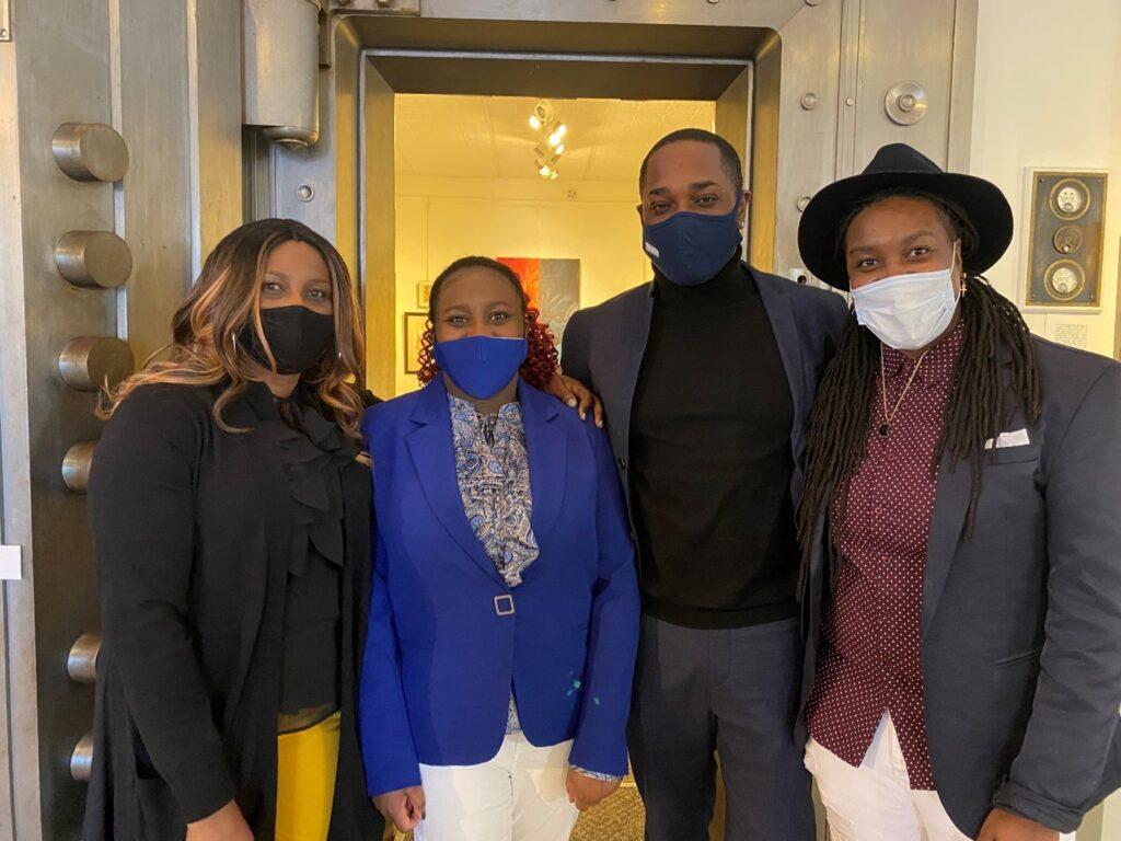 Toriann Metheney and 3 family members wearing wasks at an art exhibit