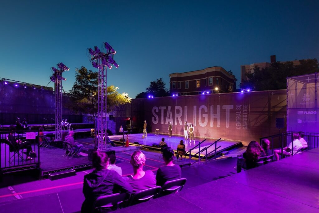 Purple stage lights cast a glow over the audience at an outdoor, evening performance at Starlight Square