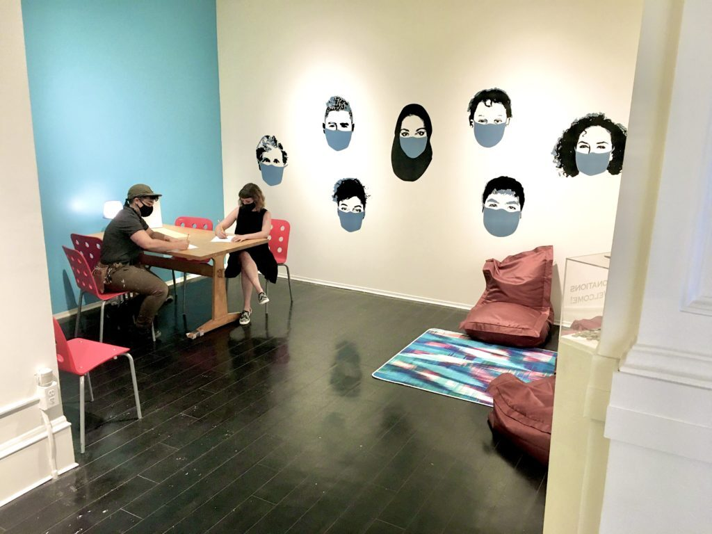 two people wearing masks sit at a table in a gallery space decorated with a mural of faces with masks