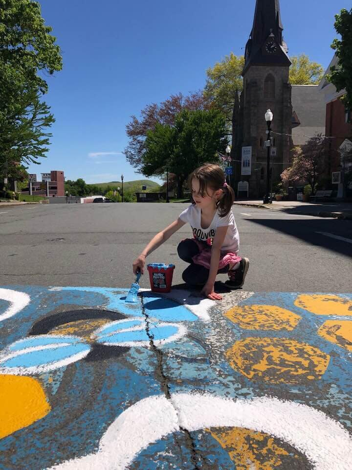 Girl painting a mural outside under a bright blue sky