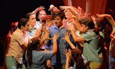 A still from a theater production in which a boy is facing forward while a circle of other young actors around him have there hands open around his head