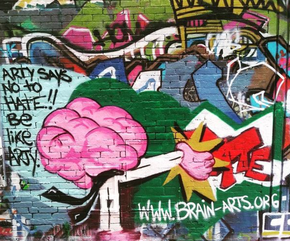 """detail of a mural painted on a brick wall. a large, pink brain with the text, """"Arty says no to hate!! Be like Arty."""""""