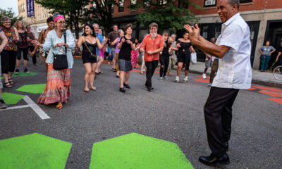 A band leader encourages a group of concert goers to dance with him in the street at a summer performance.