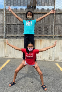 Two youth participants from Circus Up, one balancing on the other's back. Both with raised arms.