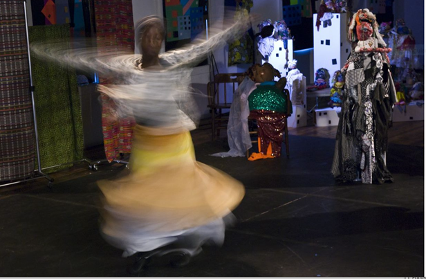A woman is a blur twirling as part of a performance. Her arms extended over her head.