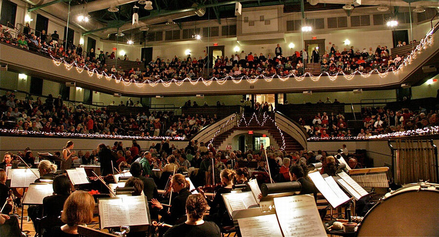 Orchestra on a stage playing for a full house.