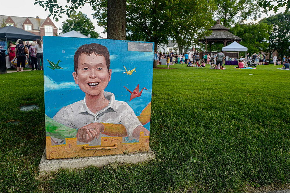 Painted utility box featuring a smiling child and grasping hands in the foreground, numerous people enjoying an outdoor event in a grassy common.