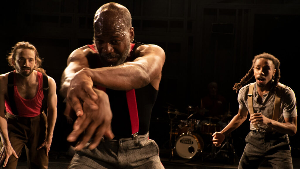 A bald male dancer with a beard wears a black sleeveless t-shirt and red suspenders. He's looking at his extended arms that cross at his hands. Two other dancers watch from the behind him.