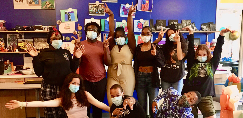 6 masked young people stand behind 3 masked kneeling young people. Their arms are making various gestures of happiness and high energy. Behind them various works on paper are hanging from a dark blue painted wall.