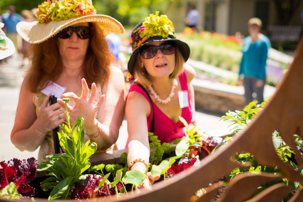 two women in floppy, floral hats and sunglasses touching plants in the Garden within Reach