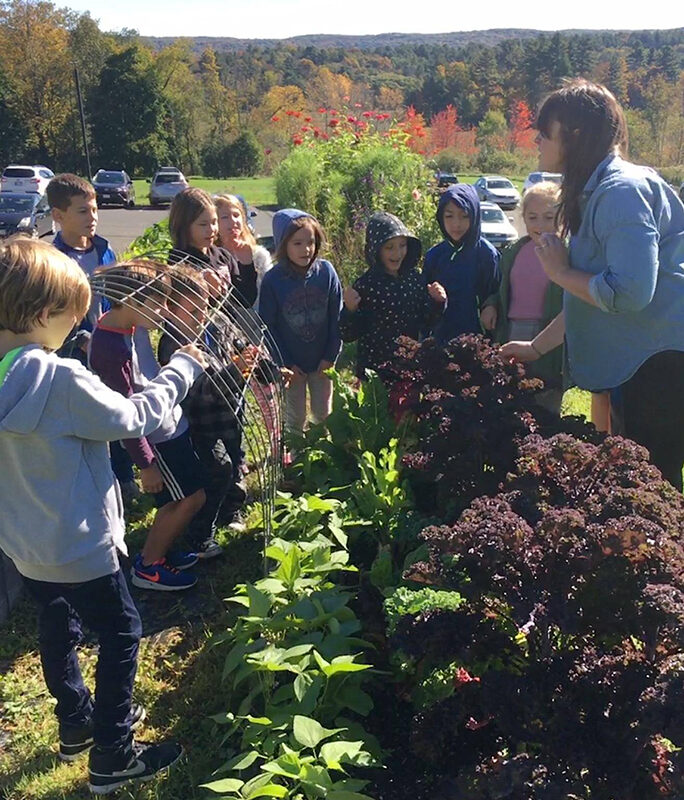 10 students stand in front of a row of cabbages and kale, mountains and fall foliage in the background